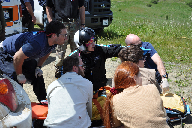 My husband, Lisa Gribi, ambulance personnel, and others carry Malachi to the helicopter.