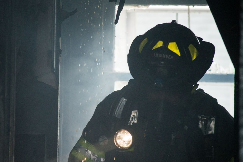 A firefighter walks through the smoke filled structure.