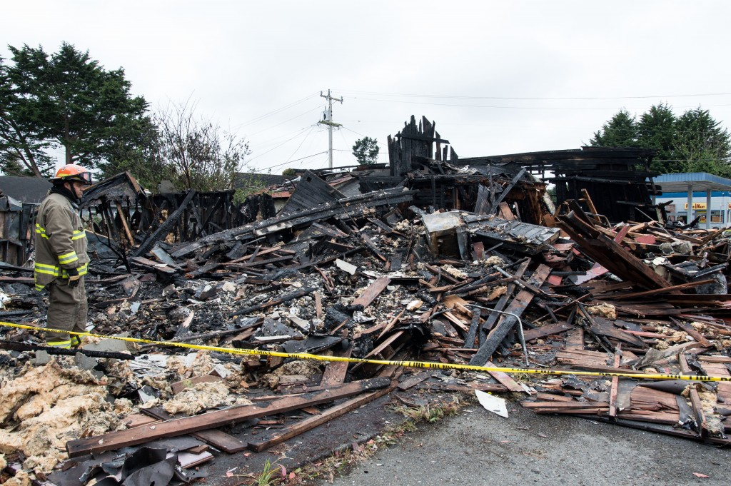 A firefighter looks over the damage from Saturday's alleged arson fire.