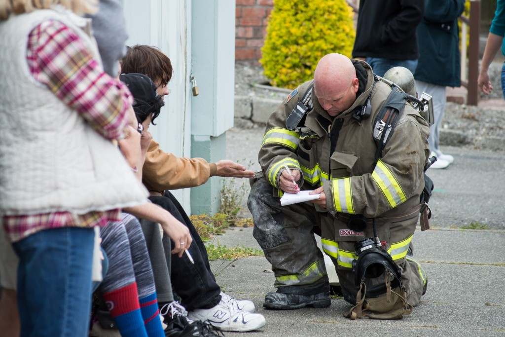 A firefighter talks to witnesses and the occupants of the house.