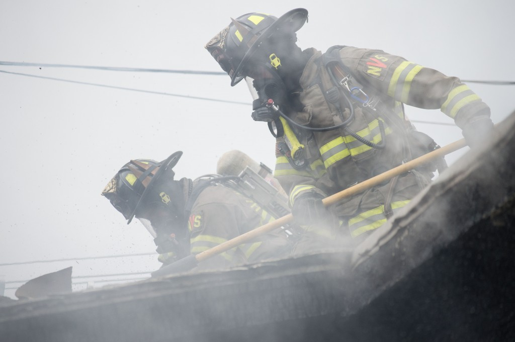 Firefighters cut holes in the roof.