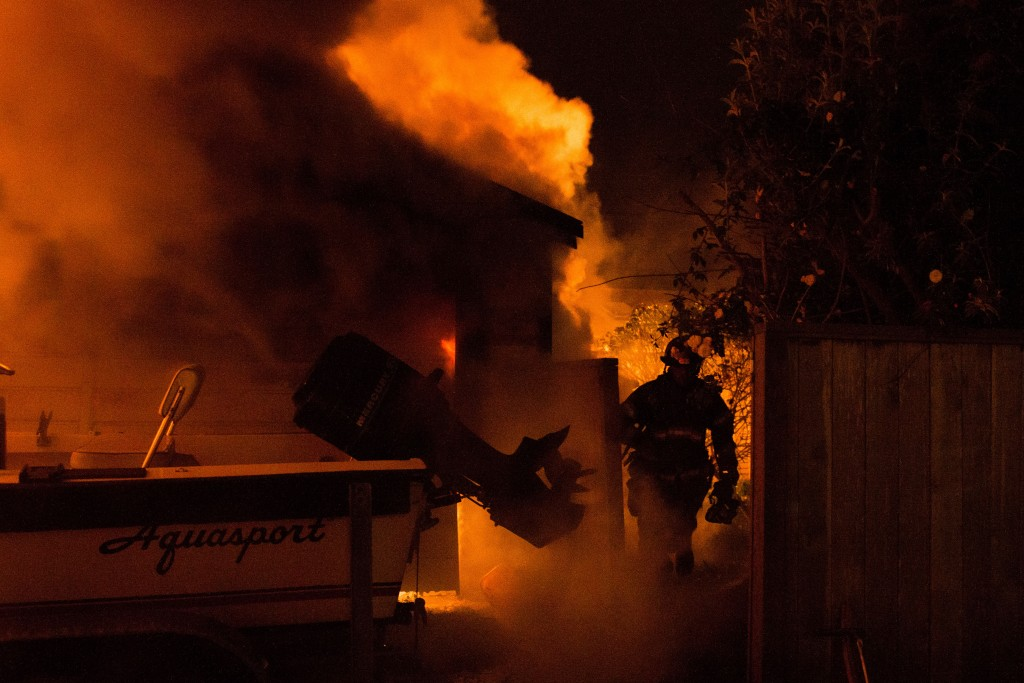 A Firefighter walks away from the flaming building.