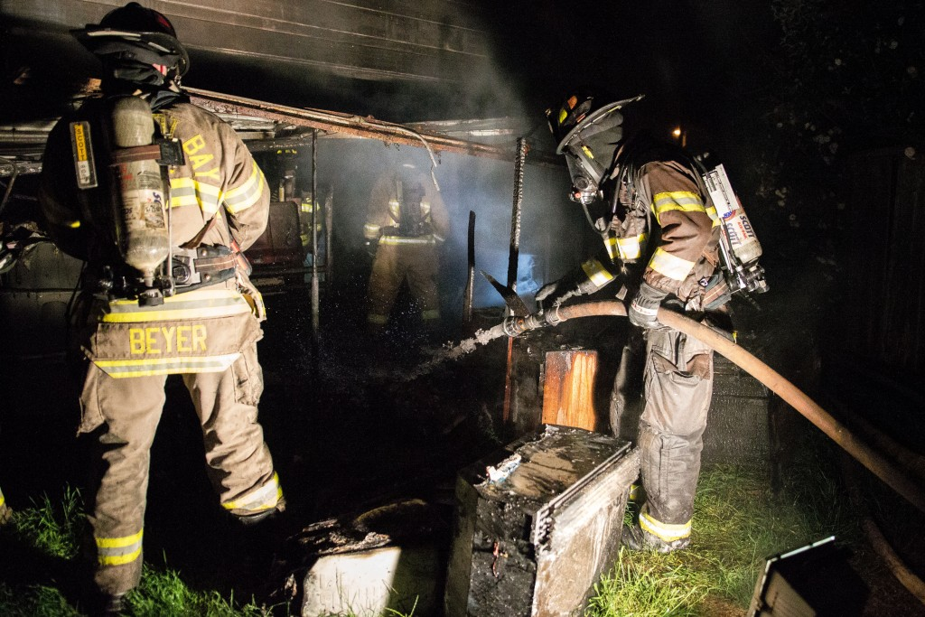 Firefighters spray the burnt contents of the structure.