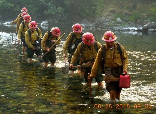 Firefighters crossing a river