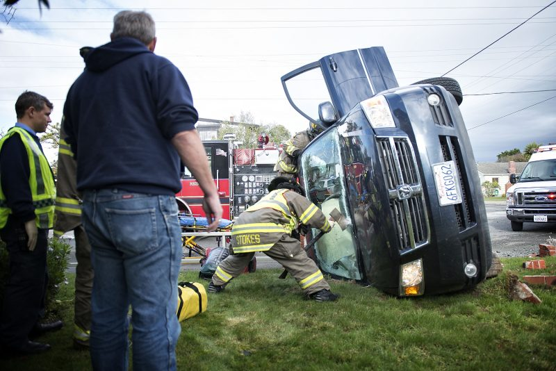 Humboldt Bay Fire crews work to extricate a woman from her van following a rollover accident at Henderson and Union in Eureka.