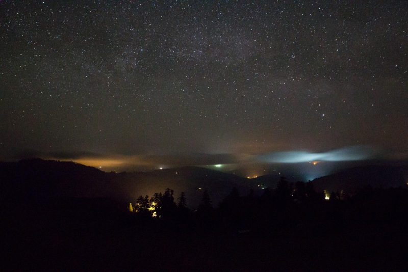 This photo was taken on the new moon in May 2016. It shows the cumulative skyglow of several lit-up greenhouses (on the other side of the ridge) reflecting off of cloud cover. [Photo by Kyle Keegan]