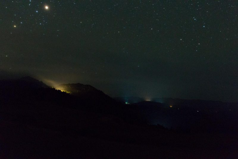 This photo was taken at 11:15pm, May 27th, 2016 from Elk Ridge looking due south. It is clear to see in this photo how the incursion of light from one factory can affect the day/night cycle of a large area. The greenhouses below in the valley shine like sports stadiums. Luckily, as summer solstice approaches many of the greenhouses shut down for a few months before starting up again in the fall. [Photo by Melissa Walbridge]