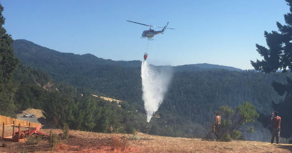 Cal Fire helicopter dropping water on Benbow Fire