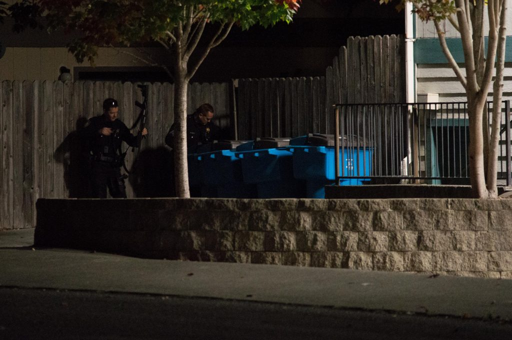 An officer adjusts his gun outside the building.