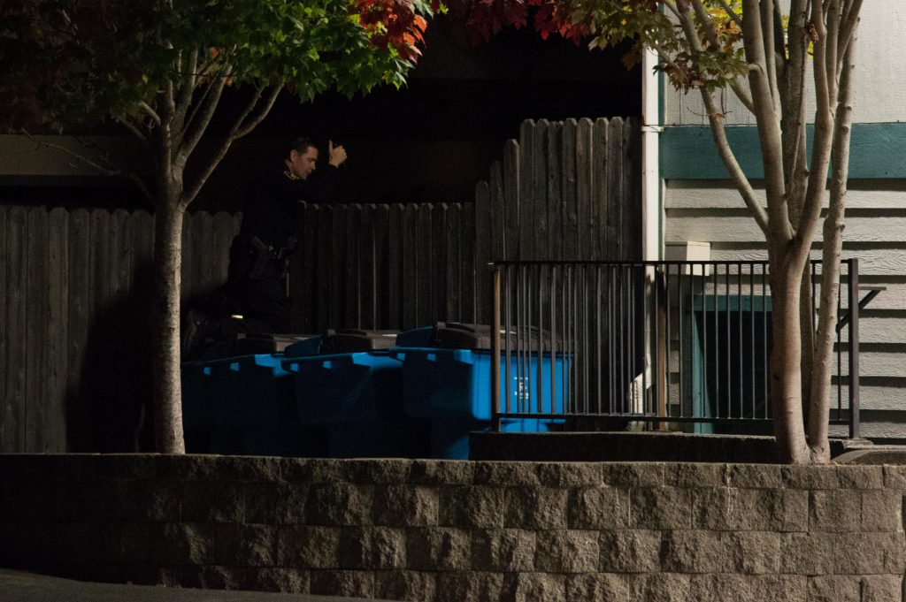 An officer peers over a fence outside the Willow Bay Apartments.