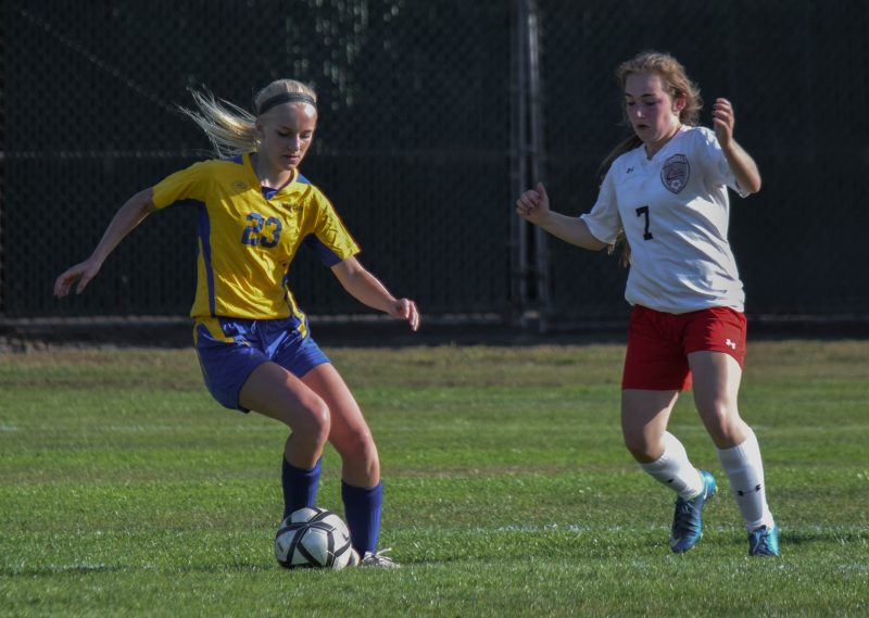 Sophomore striker Kylie Messenger (left) evades a Ferndale defender before shooting