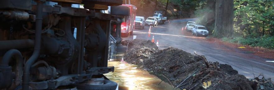 Fuel truck overturned with berm to keep leaking petroleum product from spreading.