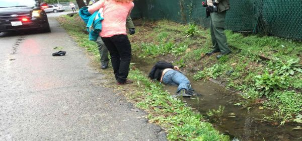 Woman and officers stand over gunshot victim in a ditch
