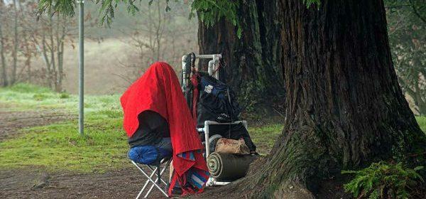Man huddles under a red blanket