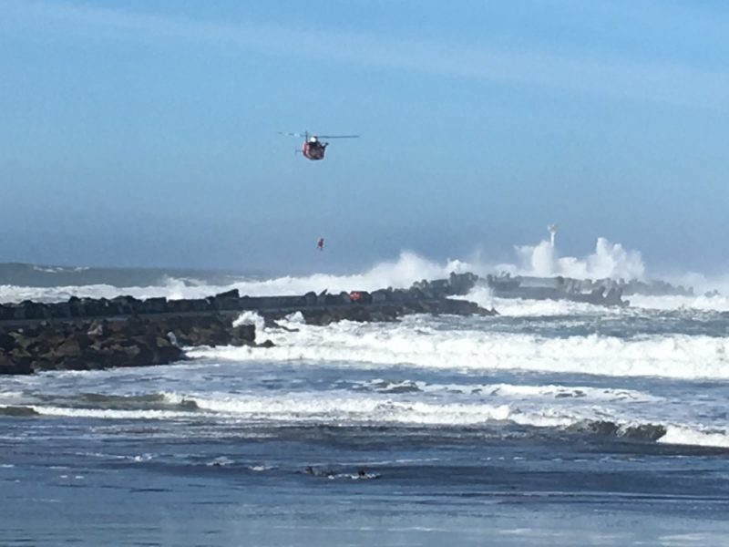 Coast Guard lifting a man from a jetty covered in waves