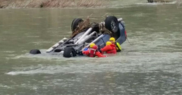 truck in river with rescuers