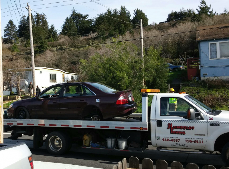 Car with burns being towed on flatbead