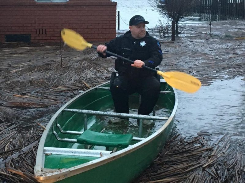 Lakeport Police officer uses a canoe to get to residents in his flooded town.