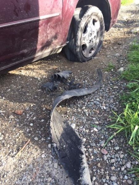 Tread from the suspect's tire twists beside the car.