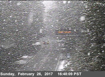 Snow falling by traffic sign carry chains