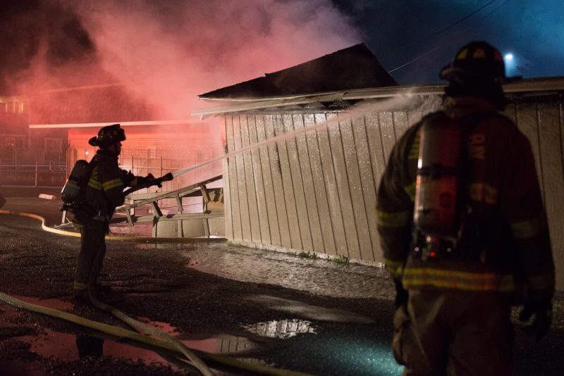 Firefighters hose down a building on fire
