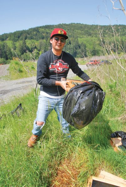 Cutline – Yurok Tribal member Gary Markussen collects debris at a recent Klamath River Clean UP.
