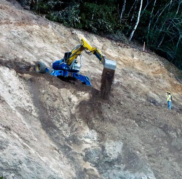 Heavy equipment operator perches his machine on the precipice