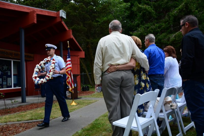 Petty Officer 3rd Class Jaykob Reed, an aviation maintenance technician assigned to Coast Guard Air Station Humboldt Bay, carries a memorial wreath past family members of a fallen flight crew at a memorial service held at Coast Guard Sector Humboldt Bay, June 8, 2017. The memorial was held on the 20th anniversary of the CG-6549 helicopter crash that killed two pilots and two crewmembers during a search-and-rescue operation. U.S. Coast Guard photo by Seaman Alex Gray.