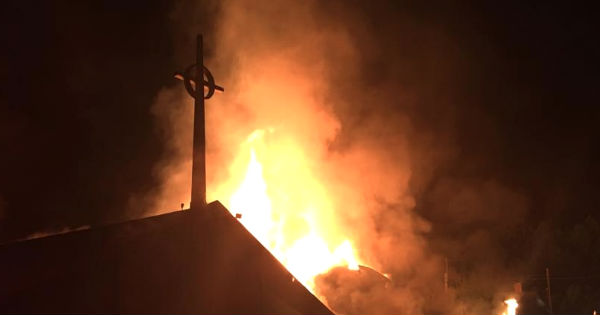Flames leap nearly as high as the church spire.