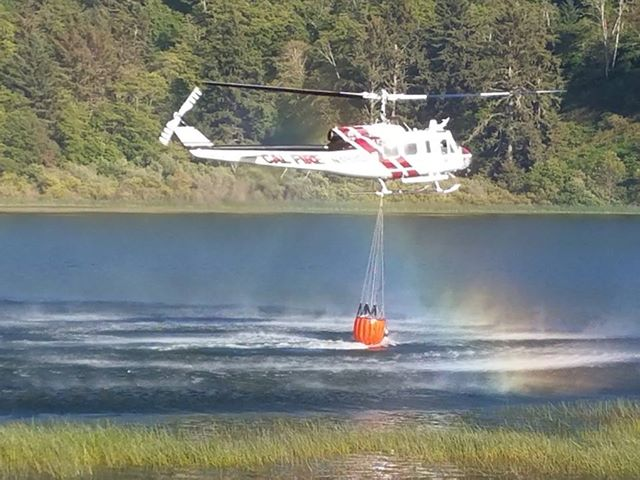 A Cal Fire helicopter dipping for water in a lagoon. [Photo by Anna Brown]