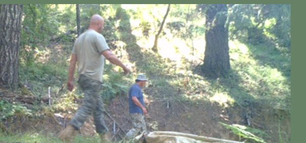 Two men on security cameras wooded area