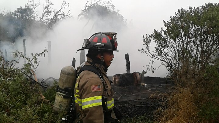 Fireman with burned structure