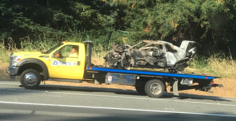Tow truck removing burned hulk of car involved in a fatal accident.