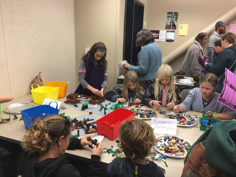 a group of girls intently building with Lego pieces.