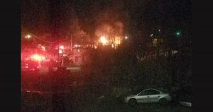 Lights from fire engines and glow of flames in a structure fire