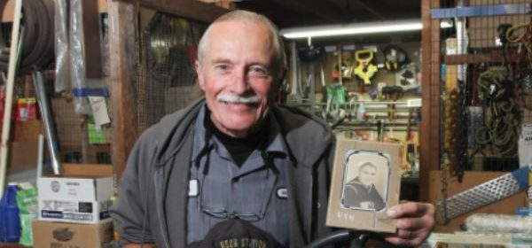veteran holding a picture of him in the military