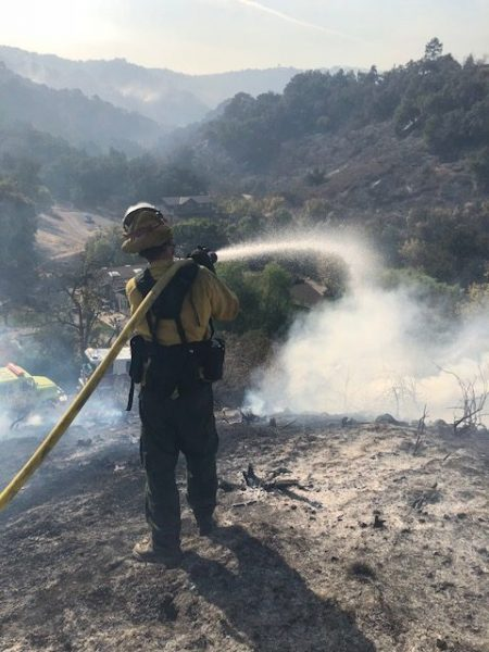 A strike team member stands on a burned hillside overlooking homes  Thomas Fire