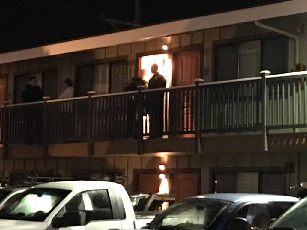 Officers speak to people on the balcony of the motel.