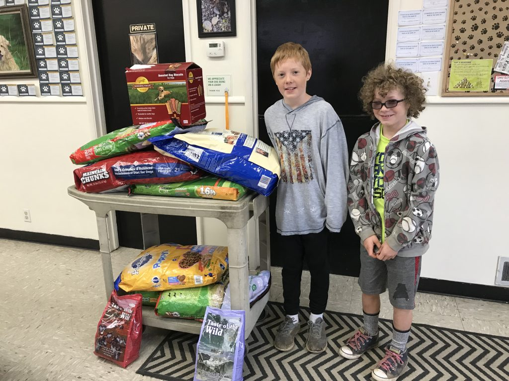 Two boys delivering pet food to animal shelter.