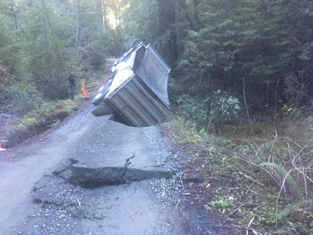 A road collapsed after a large truck hauling gravel broke through a small bridge.