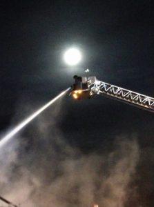 Fireman hosing down a fire from ladder under moon