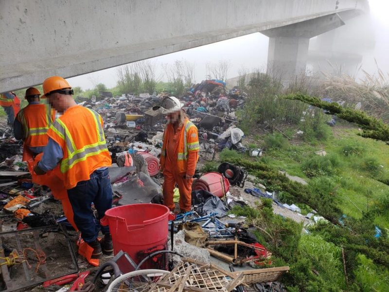Humboldt County inmate crews help clean up a homeless encampment Thursday.