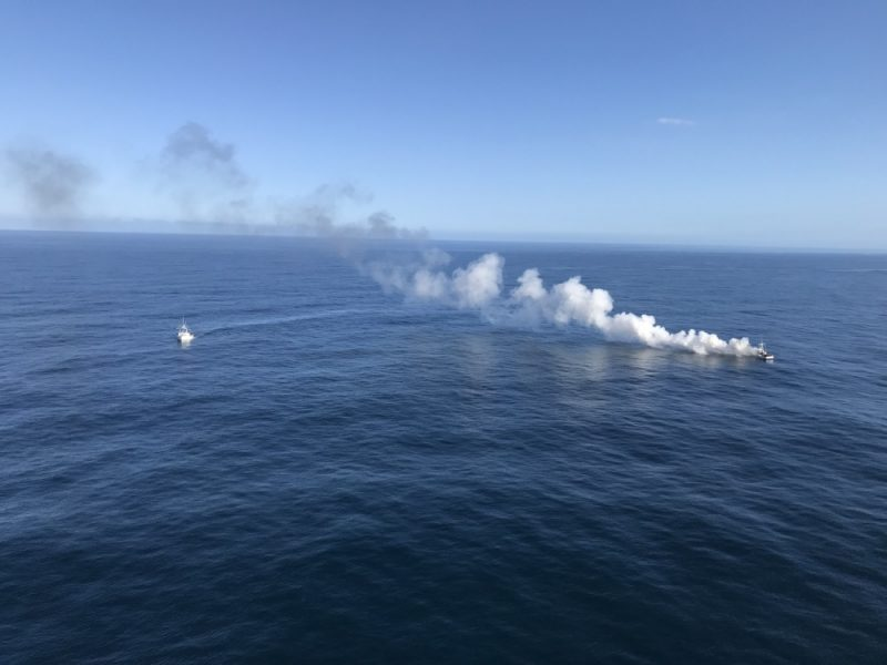 Aircrew members aboard a Coast Guard Sector Humboldt Bay MH-65 Dolphin helicopter respond to a fire aboard the commercial fishing vessel Midori near Trinidad, California, April 18, 2018. A 47-foot Motor Lifeboat crew from Station Humboldt Bay also launched to assist the vessel. (U.S. Coast Guard video/Released)
