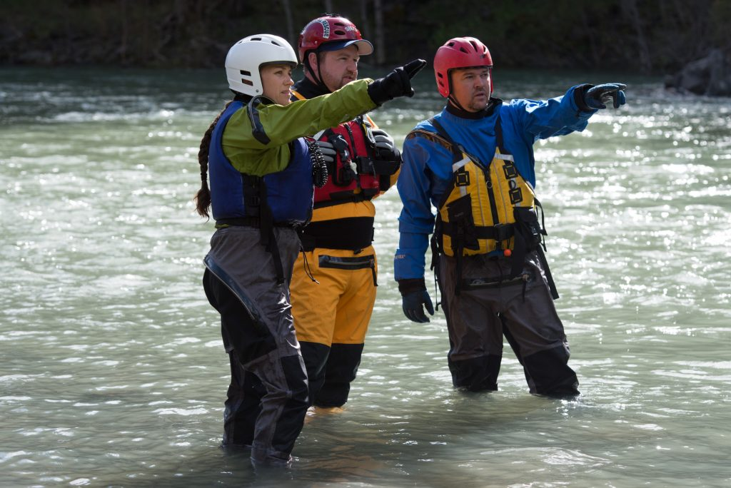 Three members of Southern Humboldt Technical Rescue--married couple Aurora and Shawn Studebaker flank Genario Gray---assess the river conditions