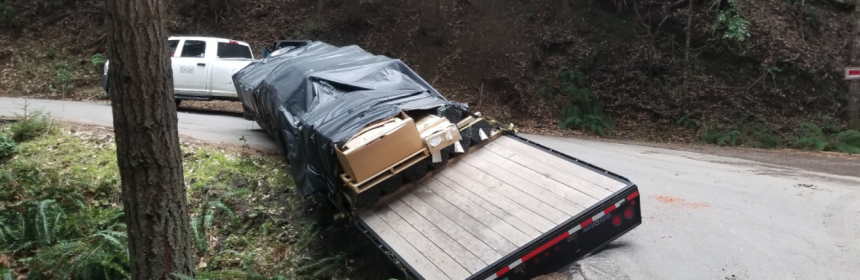 A flatbed trailer and pickup are blocking Dyerville Loop Road.
