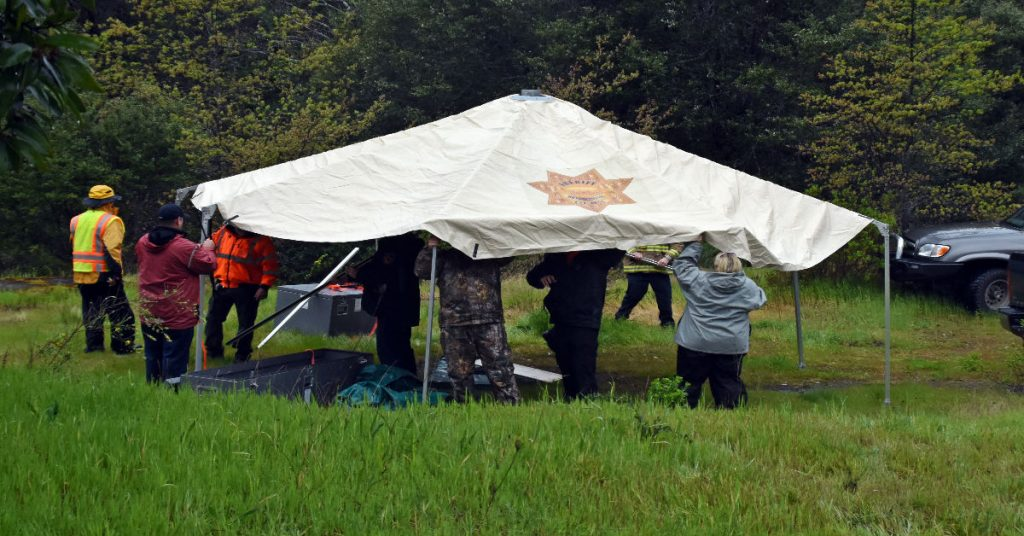 Personnel set up a tent as rain came down. Thottapilly