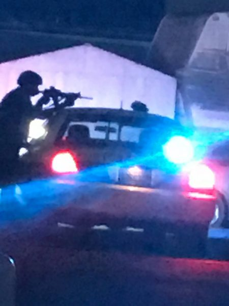 Officer uses his vehicle as a shield as he steadies his rifle.