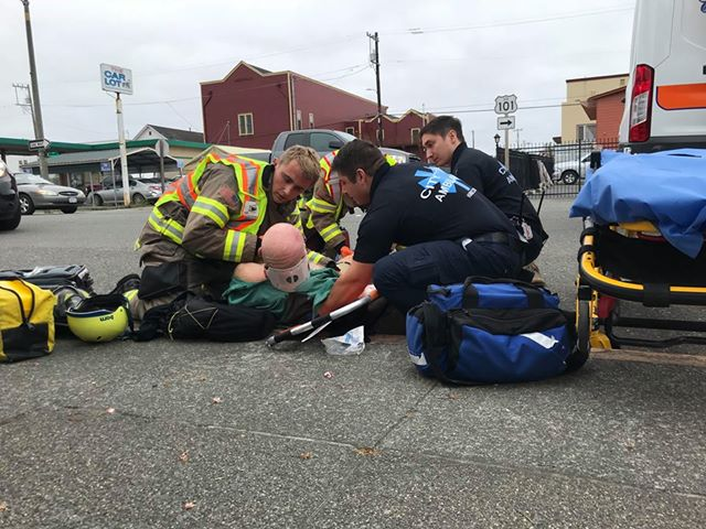 Emergency personnel prepare to lift the injured bicyclist onto a gurney.