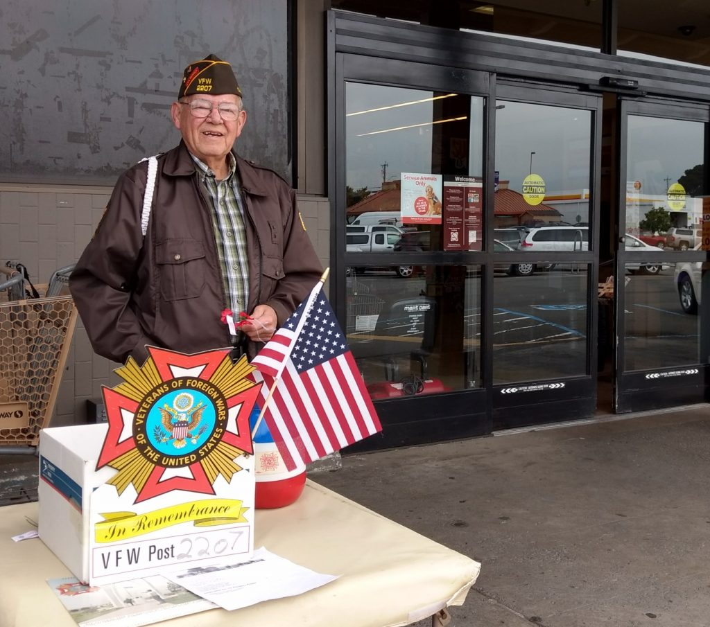 Veteran Curtis Lindley poses behind the American Flag.