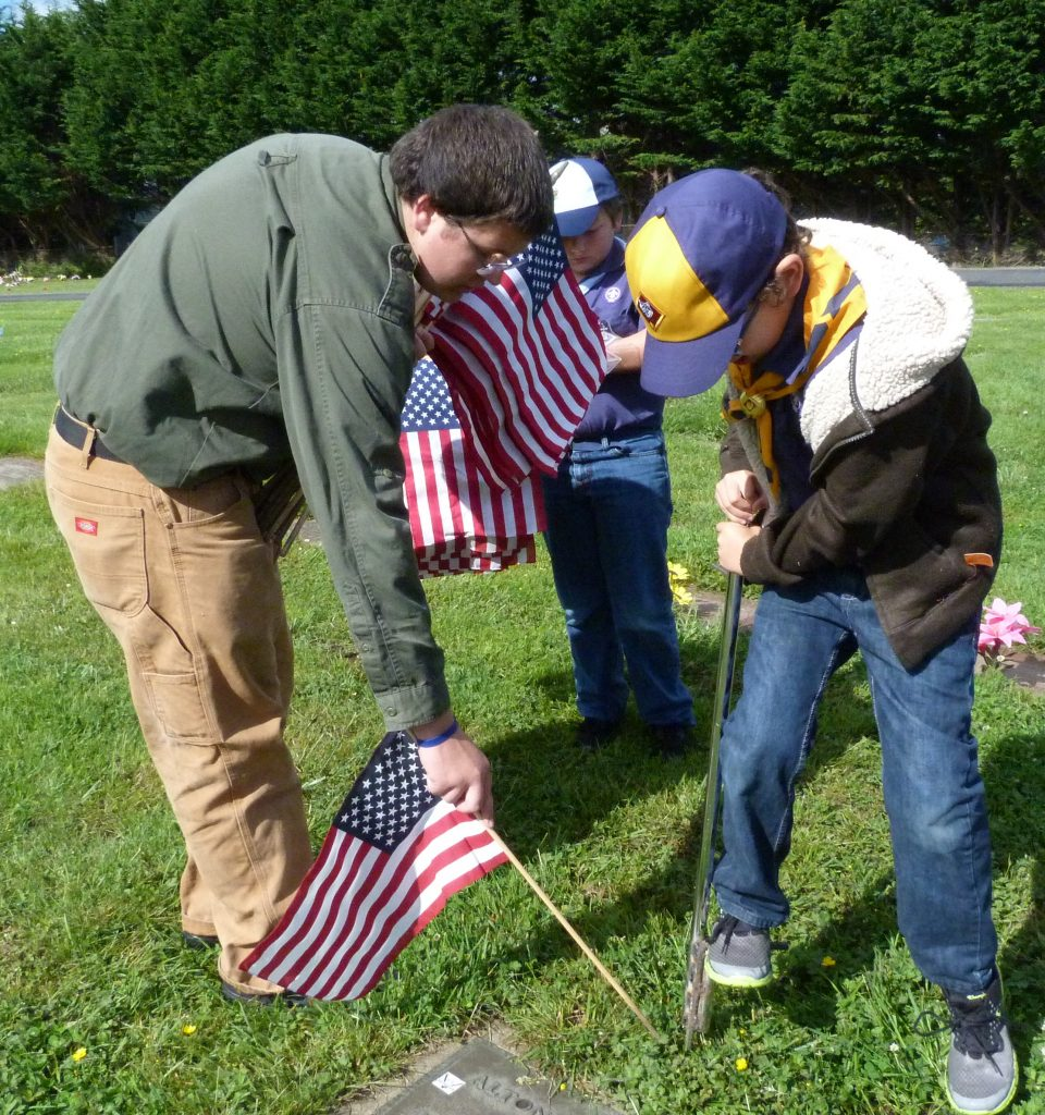 Scouts placing flags on the graves of Fortuna area veterans.